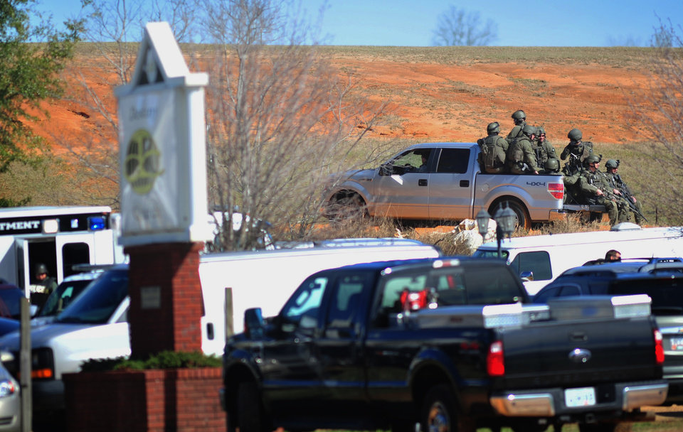 Photo - Law enforcement personnel in tactical gear ride a pickup to the scene of an ongoing hostage crisis on Friday, Feb. 1, 2013 below the site where Tuesday's school bus shooting suspect is barricaded in a bunker holding a five-year-old boy captive. More than three days after authorities said a gunman shot a school bus driver dead, grabbed a kindergartner and slipped into an underground bunker, the man showed no signs Friday of turning himself over to police. (AP Photo/The Dothan Eagle, Jay Hare)