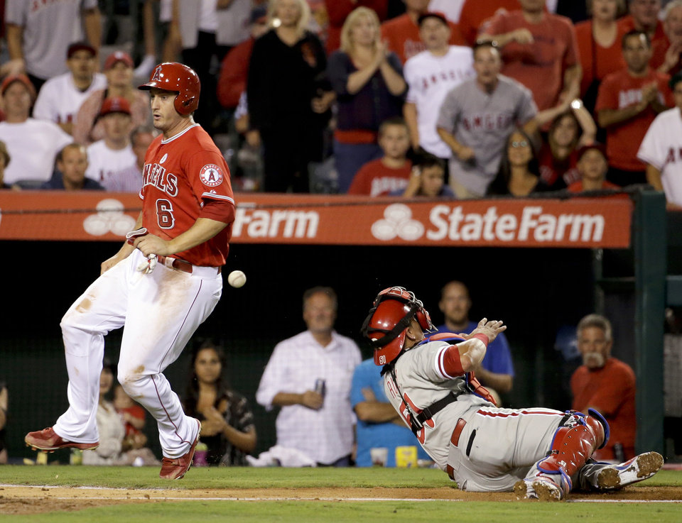 Photo - Los Angeles Angels' David Freese, left, scores past Philadelphia Phillies catcher Carlos Ruiz on a hit by Chris Iannetta during the sixth inning of a baseball game in Anaheim, Calif., Tuesday, Aug. 12, 2014. (AP Photo/Chris Carlson)