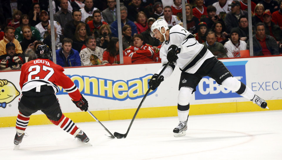 Photo - Los Angeles Kings center Jeff Carter, right, shoots on goal past Chicago Blackhawks defenseman Johnny Oduya (27), of Sweden, during the first period of an NHL hockey game, Monday, March 25, 2013, in Chicago. (AP Photo/Charles Rex Arbogast)