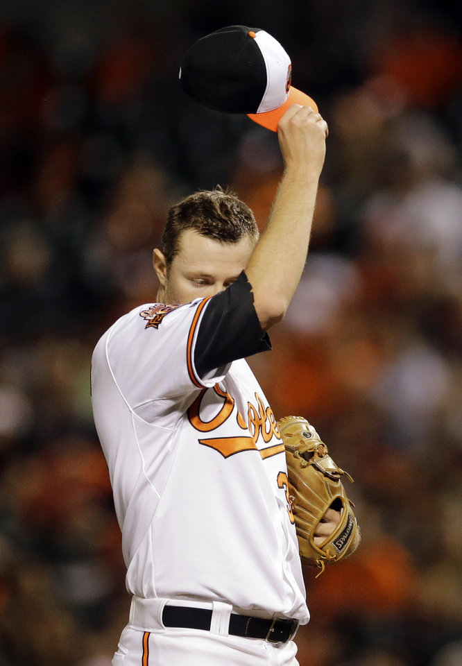 Photo - Baltimore Orioles starting pitcher Chris Tillman wipes his face in the first inning of the second baseball game of a doubleheader against the Pittsburgh Pirates, Thursday, May 1, 2014, in Baltimore. (AP Photo/Patrick Semansky)