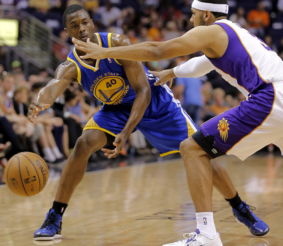 Golden State Warriors' Harrison Barnes (40) passes around Phoenix Suns' Jared Dudley during the first half of an NBA basketball game on Friday, April 5, 2013, in Phoenix. (AP Photo/Matt York)