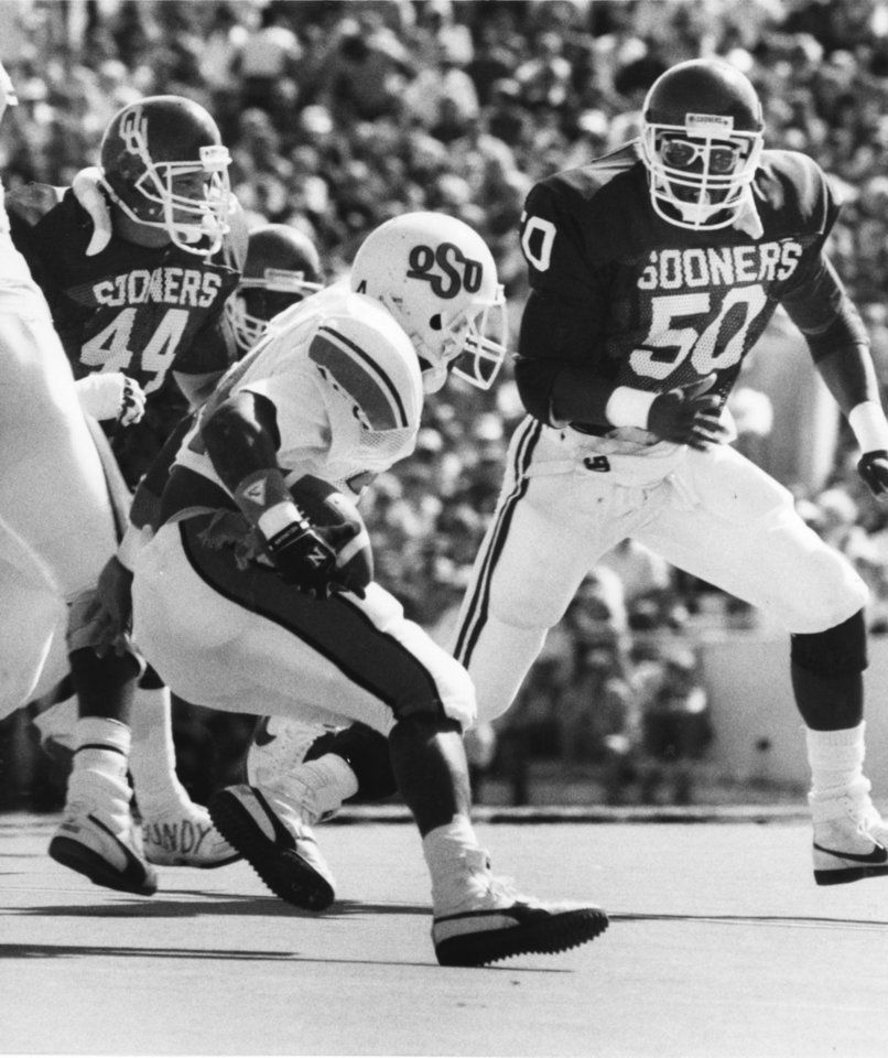 Photo - OU linebackers Brian Bosworth (44) and Dante Jones (50) converge on Oklahoma State's Thurman Thomas before he can find any room to run as the Sooners beat the Cowboys 19-0 during the Bedlam football game of Oct. 18, 1986 in Norman, Okla. Staff photo by George R. Wilson