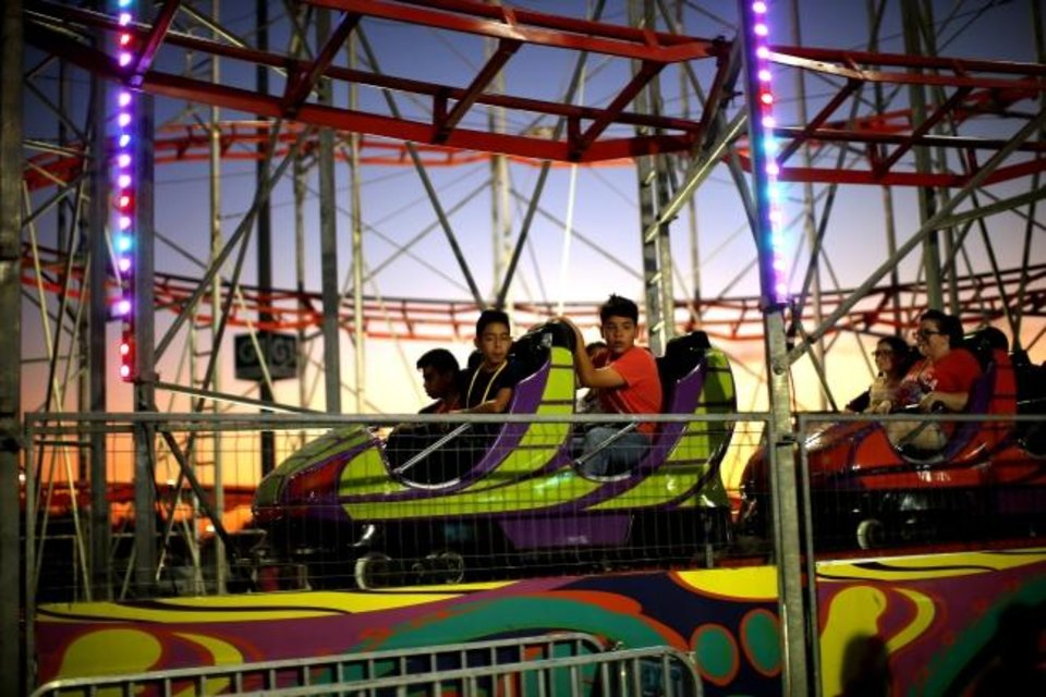 Photo -  Children ride a roller coaster at the OKC Fairgrounds during the Oklahoma State Fair. [Bryan Terry/The Oklahoman]