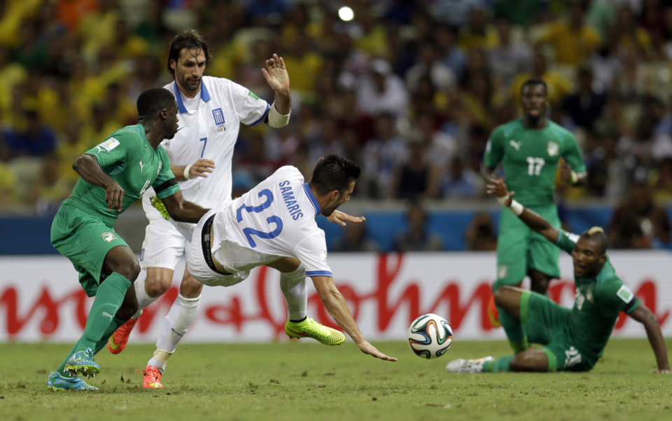 Photo - Greece's Andreas Samaris, center, is tackled by Ivory Coast's Kolo Toure, left, during the group C World Cup soccer match between Greece and Ivory Coast at the Arena Castelao in Fortaleza, Brazil, Tuesday, June 24, 2014. (AP Photo/Natacha Pisarenko)