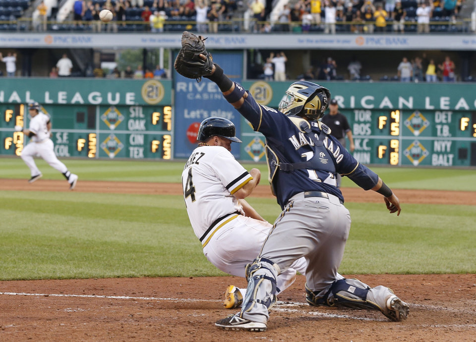 Photo - Milwaukee Brewers catcher Martin Maldonado, right, reaches for the throw as Pittsburgh Pirates' Gaby Sanchez, left, scores from third on a pinch-hit by Russell Martin in the fourteenth inning of the baseball game on Sunday, June 30, 2013, in Pittsburgh. The Pirates won 2-1, in 14 innings. (AP Photo/Keith Srakocic)
