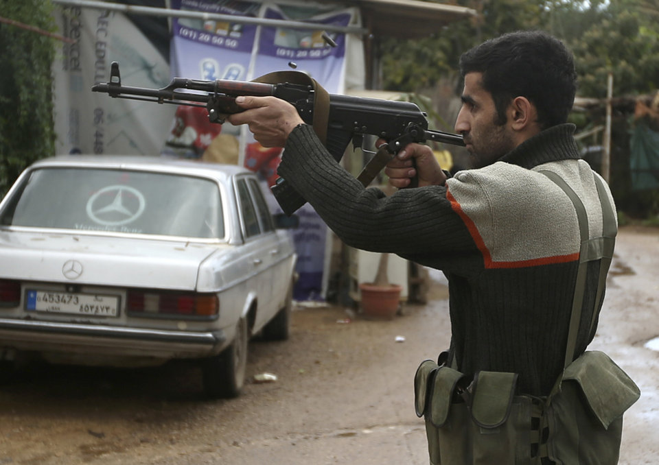 A Sunni gunman fires his weapon during clashes that erupted between pro and anti-Syrian regime gunmen in the northern port city of Tripoli, Lebanon, Wednesday, Dec. 5, 2012. Gunmen loyal to opposite sides in neighboring Syria's civil war battled in the streets of northern Lebanon at a time of deep uncertainty in Syria, with rebels closing in on President Bashar Assad's seat of power in Damascus. (AP Photo/Hussein Malla)