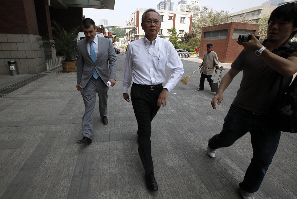Photo -   Robert S. Wang, center, deputy chief of mission at the U.S. embassy in Beijing, walks with an unidentified U.S. embassy staff outside the hospital where blind activist lawyer Chen Guangcheng is recuperating in Beijing Friday, May 4, 2012. The blind Chinese activist at the center of a diplomatic standoff between the United States and China said Friday his situation is
