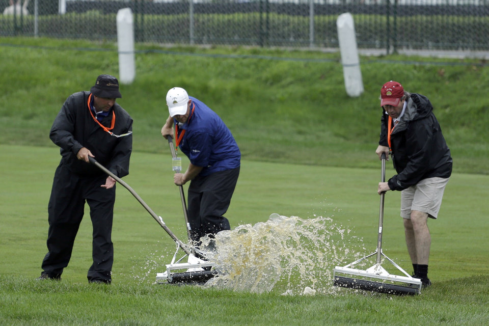 Photo - Course workers clear water from the second fairway after a weather delay during the first round of the U.S. Open golf tournament at Merion Golf Club, Thursday, June 13, 2013, in Ardmore, Pa. (AP Photo/Darron Cummings)