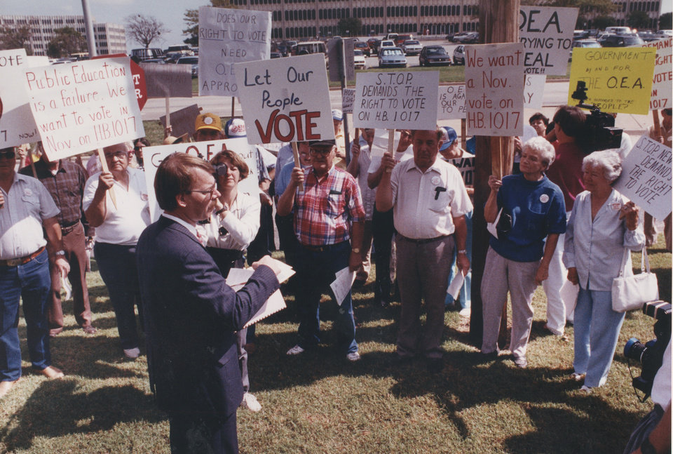 Photo - On Oct. 1, 1990, Dan Brown, head of the STOP New Taxes organization, spoke to supporters outside the Oklahoma Education Association headquarters. STOP New Taxes members accused the OEA of being behind a legal action challenging the group's initiative petition to repeal House Bill 1017, the education reform and tax law. [Photo by Paul Hellstern, The Oklahoman Archives]