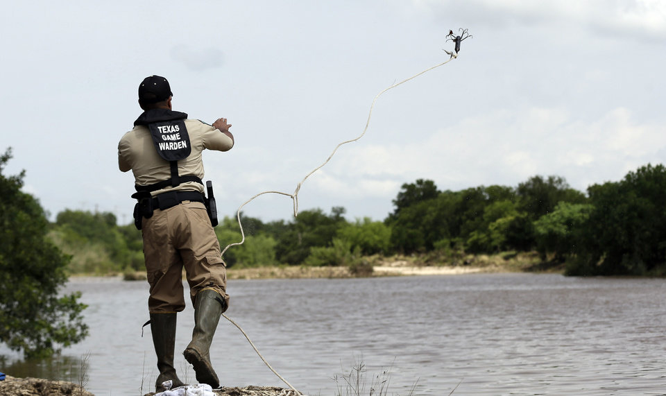 Photo - Members of the Texas Parks and Wildlife use a grappling hook to search Sunday, May 26, 2013, in Shertz, Texas, for a missing teen who was swept away in a rain swollen Cibilo Creek Saturday. (AP Photo/Eric Gay)