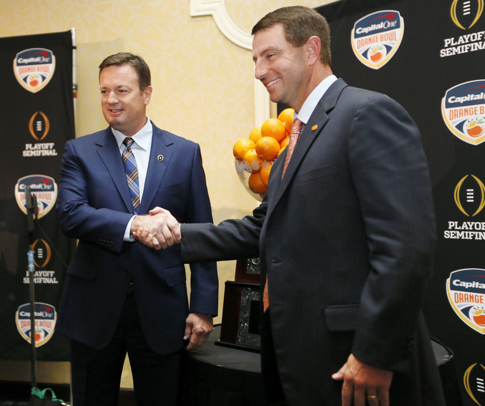 Photo - OU coach Bob Stoops, left, and Clemson coach Dabo Swinney shake hands while posing for photos during a news conference for the Capital One Orange Bowl, a College Football Playoff Semifinal game, at the Renaissance Fort Lauderdale Cruise Port Hotel in Fort Lauderdale, Florida, Wednesday, Dec. 30, 2015. The Oklahoma Sooners will play the Clemson Tigers on News Year's Eve. Photo by Nate Billings, The Oklahoman