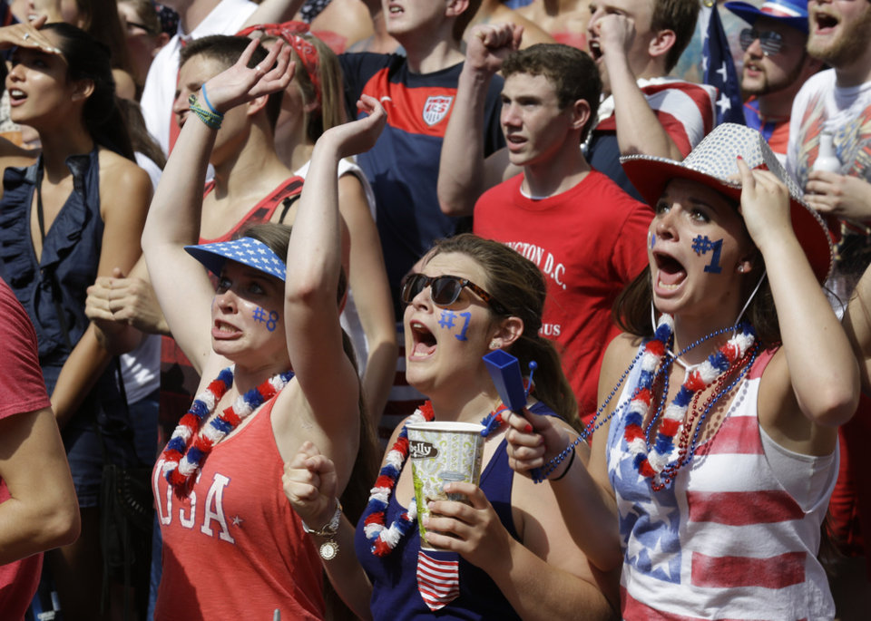Photo - Soccer fans react to a play during a World Cup match between the United States and Belgium being viewed on a large screen television, Tuesday, July 1, 2014, on Fountain Square in downtown Cincinnati. (AP Photo/Al Behrman)