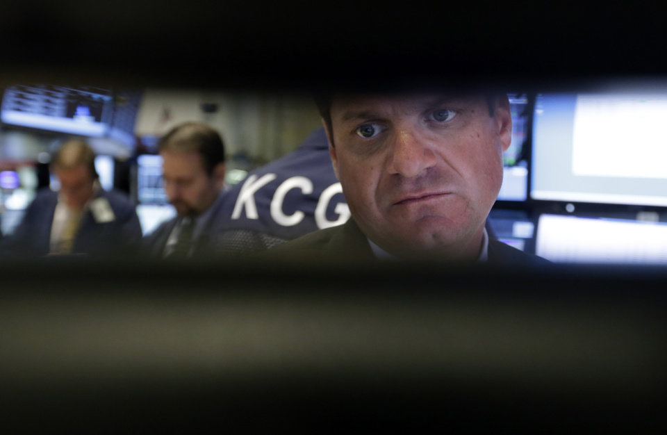 Photo - FILE - In this Wednesday, Sept. 18, 2013, file photo, specialist Michael Guli, right, is framed by his monitors as he works at his post on the floor of the New York Stock Exchange. Global stock markets fell Wednesday, Sept. 25, 2013 dragged down by fears that political gridlock in Washington over the federal budget might shut down the U.S. government. (AP Photo/Richard Drew)
