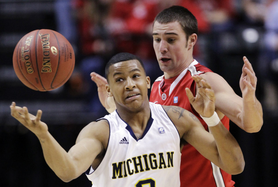 Photo -   Michigan guard Trey Burke (3) battles for a loose ball against Ohio State guard Aaron Craft (4) in the first half of an NCAA college basketball game in the semifinals of the Big Ten Conference tournament in Indianapolis, Saturday, March 10, 2012. (AP Photo/Michael Conroy)