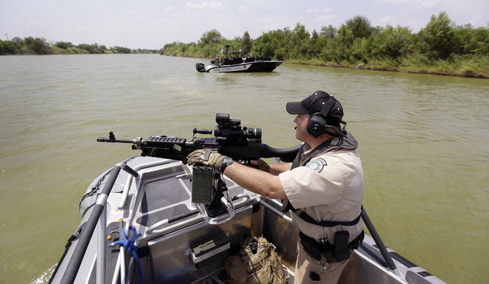 Photo - AP10ThingsToSee - A Texas Parks and Wildlife Warden stands next to a 30 caliber rifle as he patrols the Rio Grand on the U.S.-Mexico border, Thursday, July 24, 2014, in Mission, Texas. (AP Photo/Eric Gay, Pool)