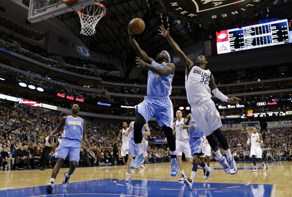 Photo - Denver Nuggets small forward Jordan Hamilton, left, watches as point guard Ty Lawson (3) goes up for a shot-attempt as Dallas Mavericks' O.J. Mayo (32) defends in the first half of an NBA basketball game on Friday, Dec. 28, 2012, in Dallas. (AP Photo/Tony Gutierrez)