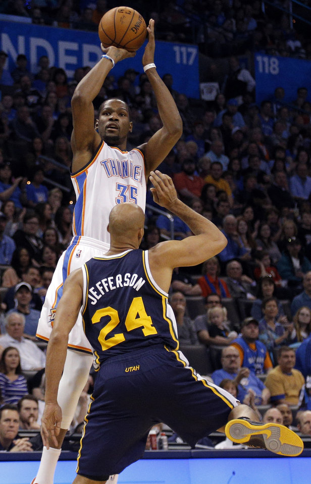 Photo - Oklahoma City 's Kevin Durant (35) shoots a three-point basket over Utah's Richard Jefferson (24) during the NBA game between the Oklahoma City Thunder and the Utah Jazz at the Chesapeake Energy Arena, Sunday, March 30, 2014, in Oklahoma City. Photo by Sarah Phipps, The Oklahoman