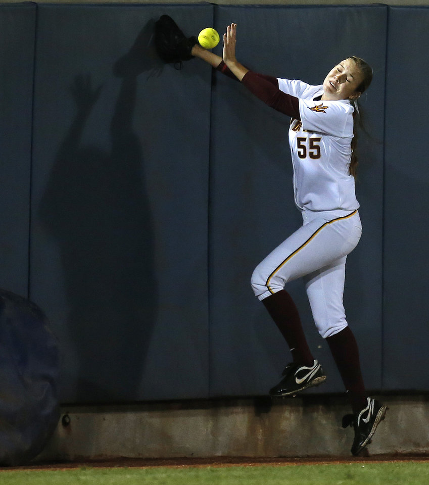 Arizona State's Elizabeth Caporuscio runs into the outfield wall as she tries to catch a foul ball against Michigan during a Women's College World Series softball game at ASA Hall of Fame Stadium in Oklahoma City, Sunday, June, 2, 2013. Photo by Bryan Terry, The Oklahoman