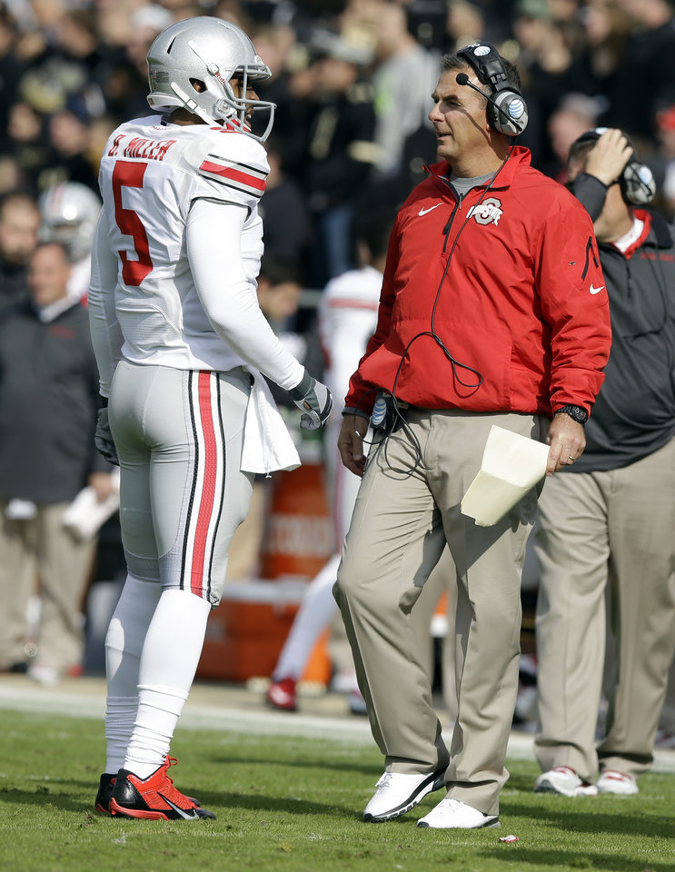 Photo - Ohio State quarterback Braxton Miller, left, talks with head coach Urban Meyer during the first half of an NCAA college football game against Purdue in West Lafayette, Ind., Saturday, Nov. 2, 2013. (AP Photo/Michael Conroy)