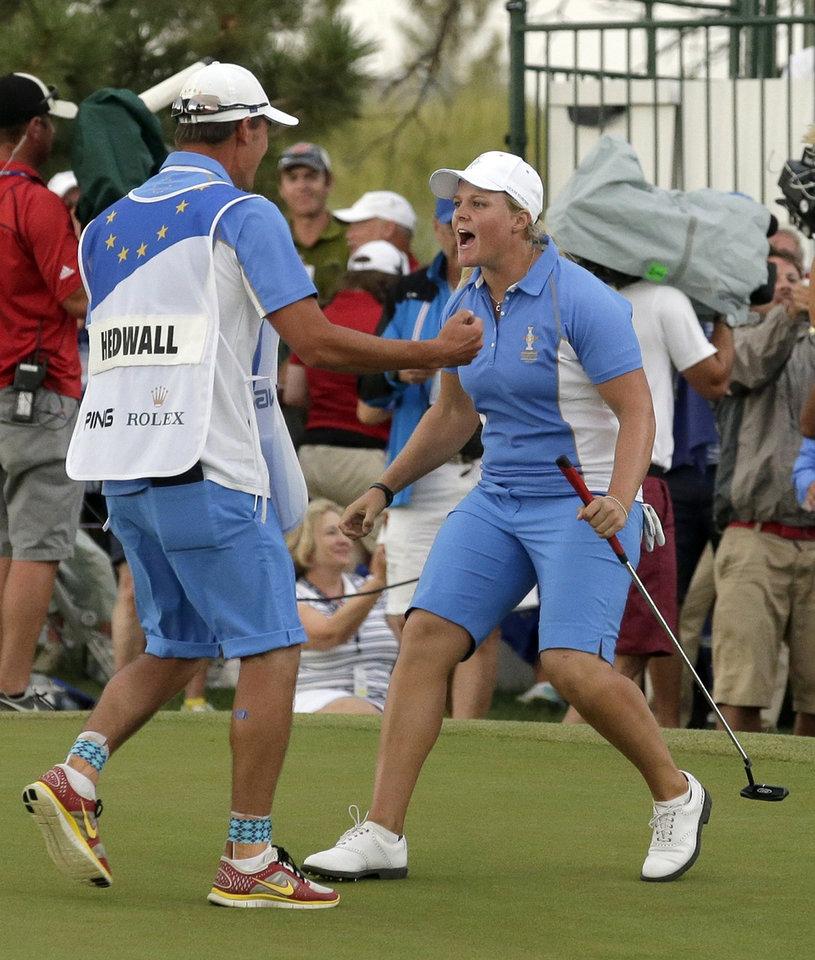 Photo - Europe's Caroline Hedwall of Sweden, right, celebrates with her caddie Henrik Hilford Brander after making a birdie putt on the 18th hole to give her the win over United States' Michelle Wie during the singles matches at the Solheim Cup golf tournament Sunday, Aug. 18, 2013, in Parker, Colo. The win gave Europe 14 points and they retained the Solheim Cup. (AP Photo/Chris Carlson)