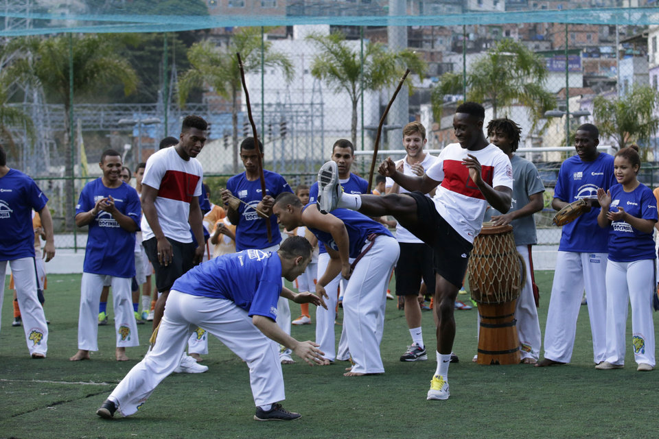Photo - England national soccer team players Danny Welbeck, center right, and Daniel Sturridge, center left, join in a Capoeira dance demonstration with locals during a visit by a five England players to the Rocinha Sports Complex on the edge of the Rocina favela in Rio de Janeiro, Brazil, Monday, June 9, 2014.  The England soccer team are staying in Rio de Janeiro as their base city for the 2014 soccer World Cup.  (AP Photo/Matt Dunham)