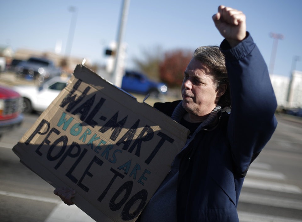 Mark Faulk stands with a sign during an Occupy OKC demonstration at a Wal-Mart in Del City, Friday, Nov. 23, 2012. Members of the Occupy movement were protesting for Wal-Mart worker\'s rights to a living wage. Photo by Garett Fisbeck, The Oklahoman