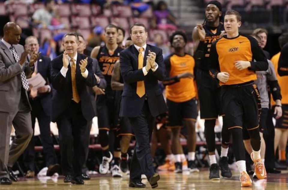 Photo - Oklahoma State head coach Travis Ford, center, watches the action in the first half of the NCAA college Orange Bowl Basketball Classic against Florida State, Saturday, Dec. 19, 2015, in Sunrise, Fla. (AP Photo/Lynne Sladky)