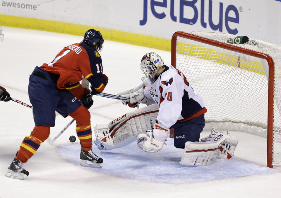 Photo - Florida Panthers center Jonathan Huberdeau, left, scores against Washington Capitals goalie Braden Holtby, during the second period of an NHL hockey game, Tuesday, Feb. 12, 2013 in Sunrise, Fla. (AP Photo/Wilfredo Lee)