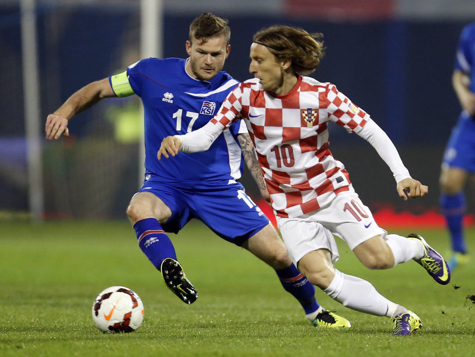 Photo - FILE - In this Nov. 19, 2013, file photo, Iceland's Aron Gunnarsson, left, is challenged by Croatia's Luka Modric during their World Cup qualifying playoff second leg soccer match in Zagreb, Croatia. (AP Photo/Darko Bandic, File)