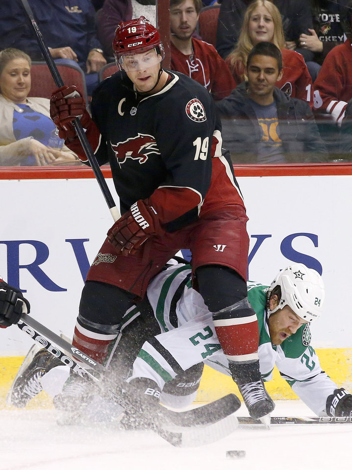 Photo - Phoenix Coyotes' Shane Doan (19) gets tangled up with Dallas Stars' Jordie Benn (24) during the second period of an NHL hockey game Tuesday, Feb. 4, 2014, in Glendale, Ariz. (AP Photo/Ross D. Franklin)