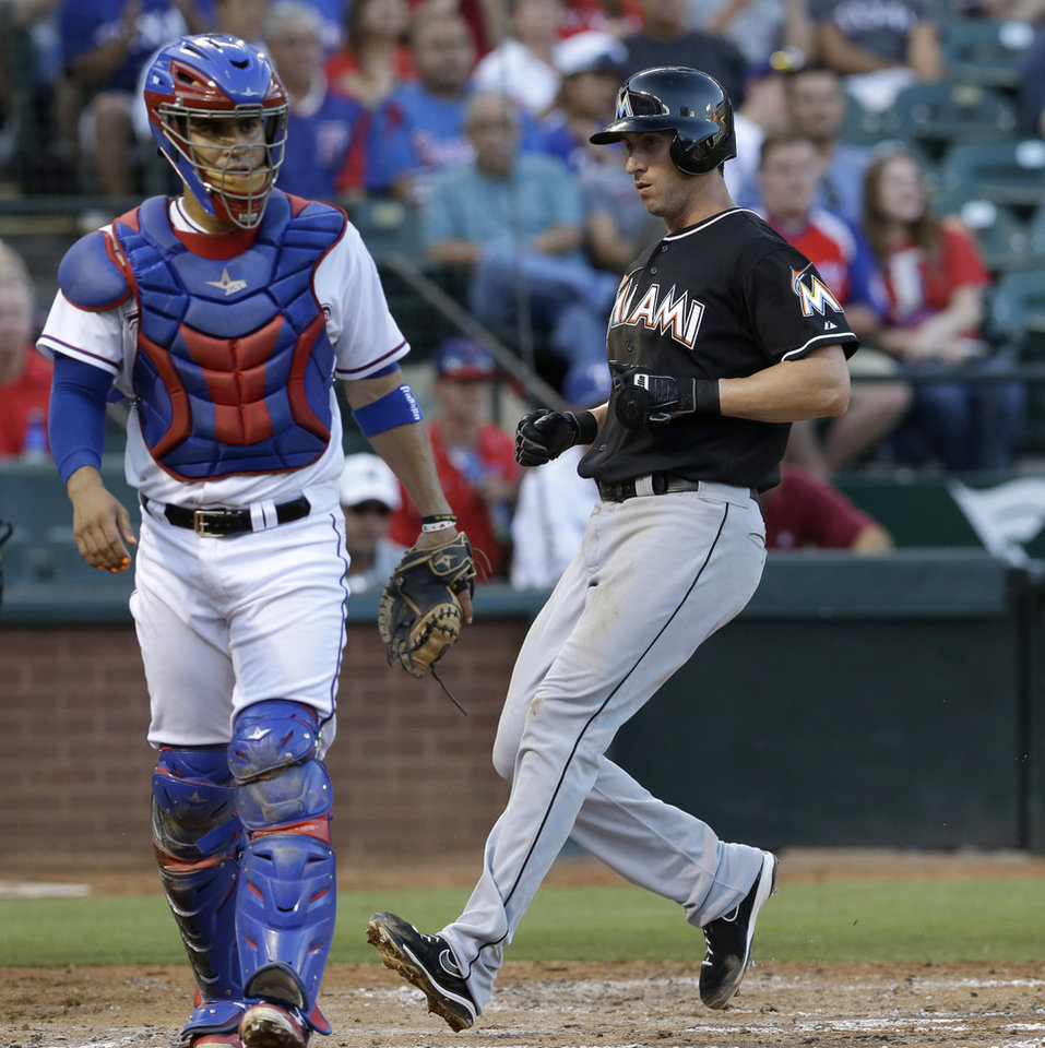 Photo - Miami Marlins Ed Lucas, right, crosses home plate from third base behind Texas Rangers catcher Robinson Chirinos (61) scoring on a ground out by teammate Garrett Jones during the second inning of a baseball game in Arlington, Texas, Tuesday, June 10, 2014. (AP Photo/LM Otero)