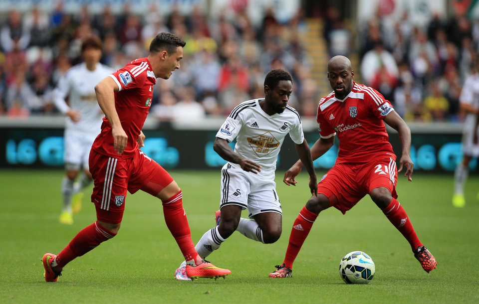 Photo - Swansea City's Nathan Dyer, center, skips over tackles from West Bromwich Albion's Youssuf Mulumbu, right, and Jason Davidson during their English Premier League soccer match at the Liberty Stadium, Swansea, Wales, Saturday, Aug. 30, 2014. (AP Photo/Nick Potts, PA Wire)    UNITED KINGDOM OUT   -   NO SALES   -   NO ARCHIVES