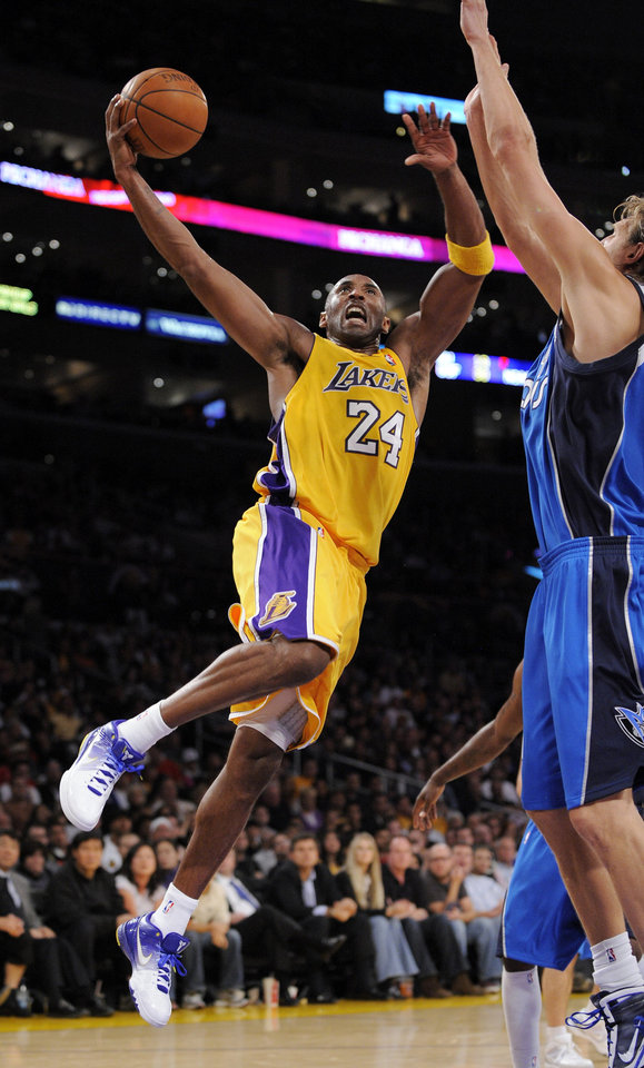 Photo - Los Angeles Lakers guard Kobe Bryant, left, puts up a shot as Dallas Mavericks forward Dirk Nowitzki defends during the second half of their NBA basketball game, Friday, Oct. 30, 2009, in Los Angeles.  (AP Photo/Mark J. Terrill) ORG XMIT: LAS107