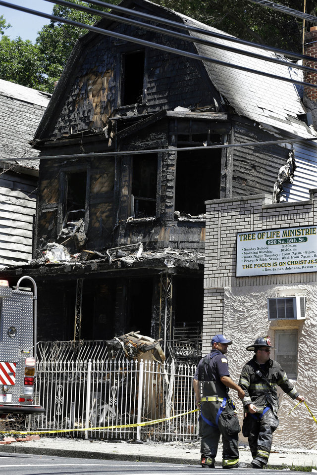 Photo - Firefighters and police work near the rubble of a burned out home as they look for clues to a fire that authorities say killed six people in Newark, N.J., Sunday, June 16, 2014. The Essex County prosecutor's office says the fast-moving fire that roared through a single-family home in New Jersey's largest city, broke out at around 4 a.m. Sunday. (AP Photo/Mel Evans)
