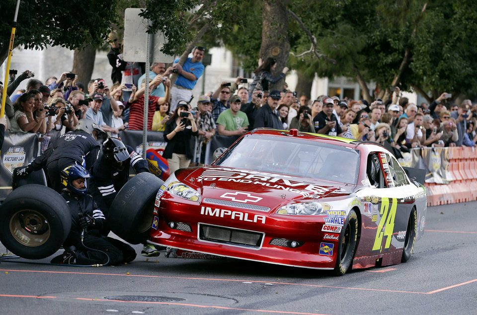 Photo - Jeff Gordon stops for a tire change while driving down the Las Vegas Strip for the Nascar Awards Week victory lap, Thursday, Nov. 29, 2012, in Las Vegas. (AP Photo/Julie Jacobson)