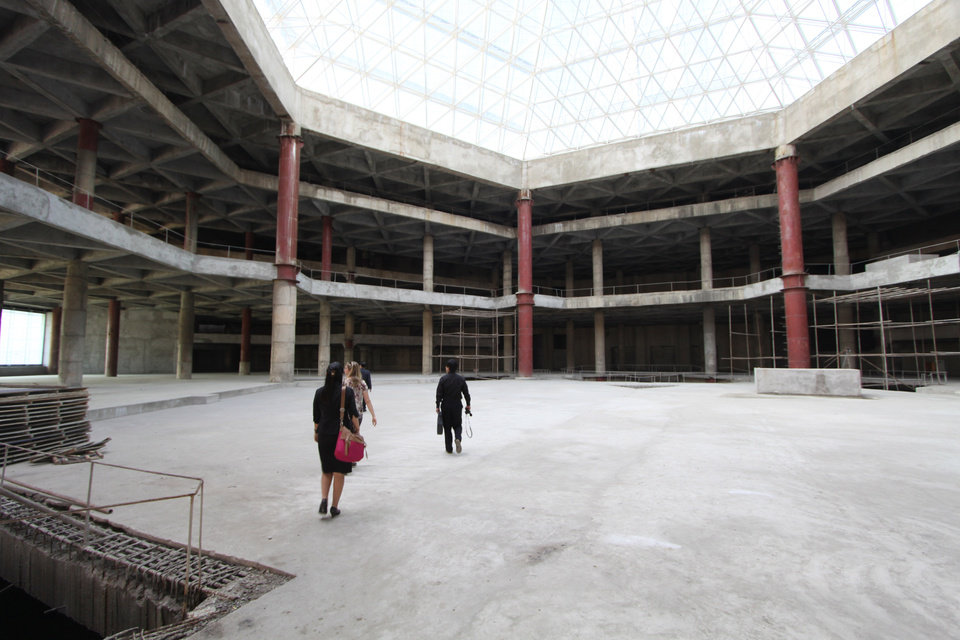 Photo -   In this Sept. 23, 2012 photo released by Koryo Group, visitors tour the top floor of the 105-story Ryugyong Hotel in Pyongyang, North Korea. After years of standing unfinished, construction on the exterior of the massive hotel resumed three years ago but the hotel has not yet opened to the public. This photo taken by the Beijing-based Koryo Tours shows that the interior remains unfinished. (AP Photo/Koryo Group) NO SALES, EDITORIAL USE ONLY