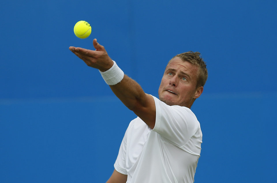 Photo - Australia's Lleyton Hewitt serves to Daniel Gimeno-Traver of Spain during their first round Queen's Club grass court tennis tournament match in London, Monday June 9, 2014. (AP Photo/Alastair Grant)