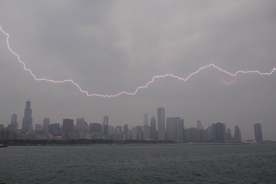 Lighting flashes over the Chicago skyline, Wednesday, June 12, 2013. An unusually massive line of storms packing hail, lightning and tree-toppling winds was rolling through the Midwest on Wednesday and could affect more than one in five Americans from Iowa to Maryland. (AP Photo/Scott Eisen)