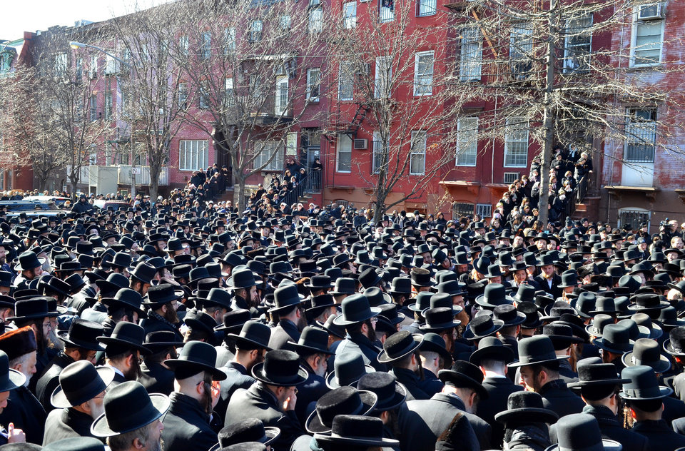 Photo - In this March 3, 2013, photo provided by VosIzNeias.com, Orthodox Jewish mourners gather outside the Congregation Yetev Lev D'Satmar synagogue in Brooklyn's Williamsburg neighborhood for the funeral of two expectant parents who were killed in a car accident early Sunday, in New York. The baby of Nachman and Raizy Glauber, a boy, was delivered prematurely by cesarean section and survived until the next morning, but died around 5:30 a.m. on Monday,March 4. Police were searching for the driver of a BMW and a passenger who fled on foot after slamming into the livery cab that was transporting the 21-year-old couple to a hospital. (AP Photo/VosIzNeias.com, Eli Wohl)