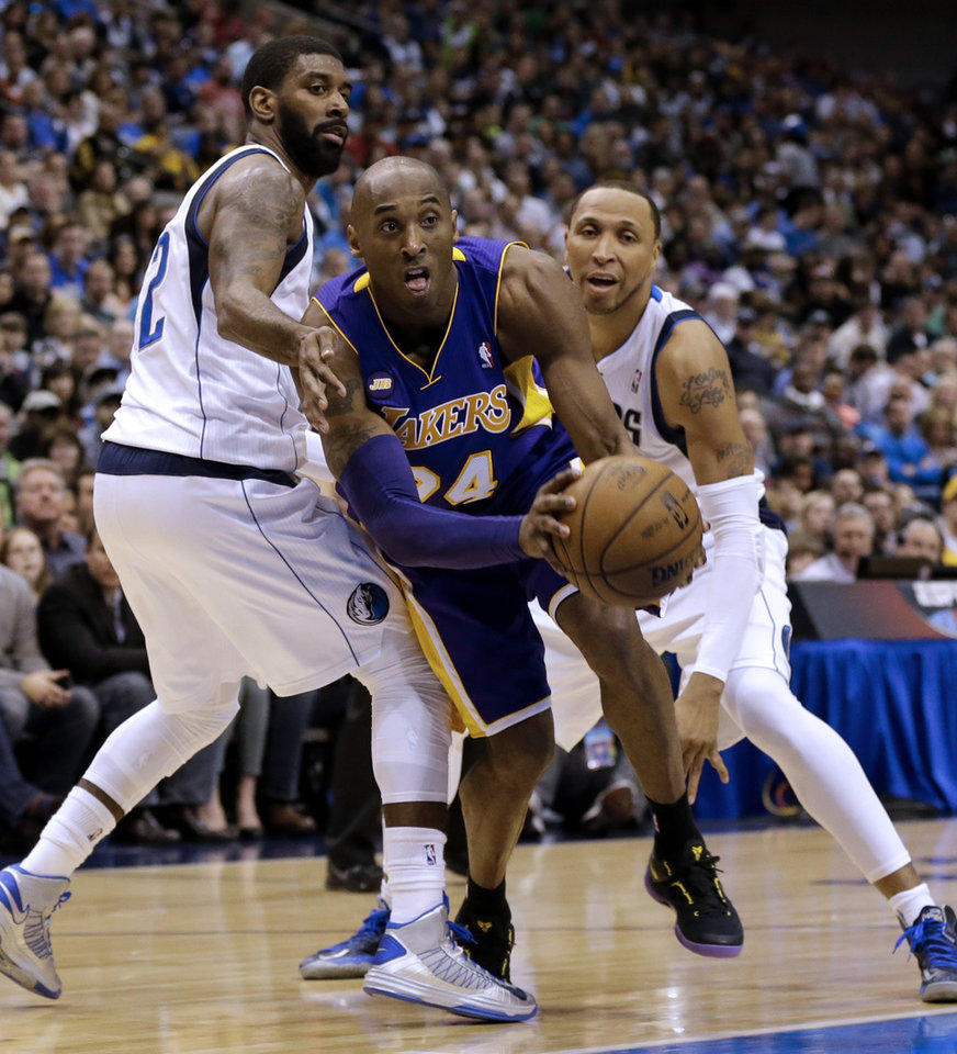 Los Angeles Lakers guard Kobe Bryant (24) drives against Dallas Mavericks' O.J. Mayo, left, and Shawn Marion, right, in the first half of an NBA basketball game Sunday, Feb. 24, 2013, in Dallas. (AP Photo/Tony Gutierrez)