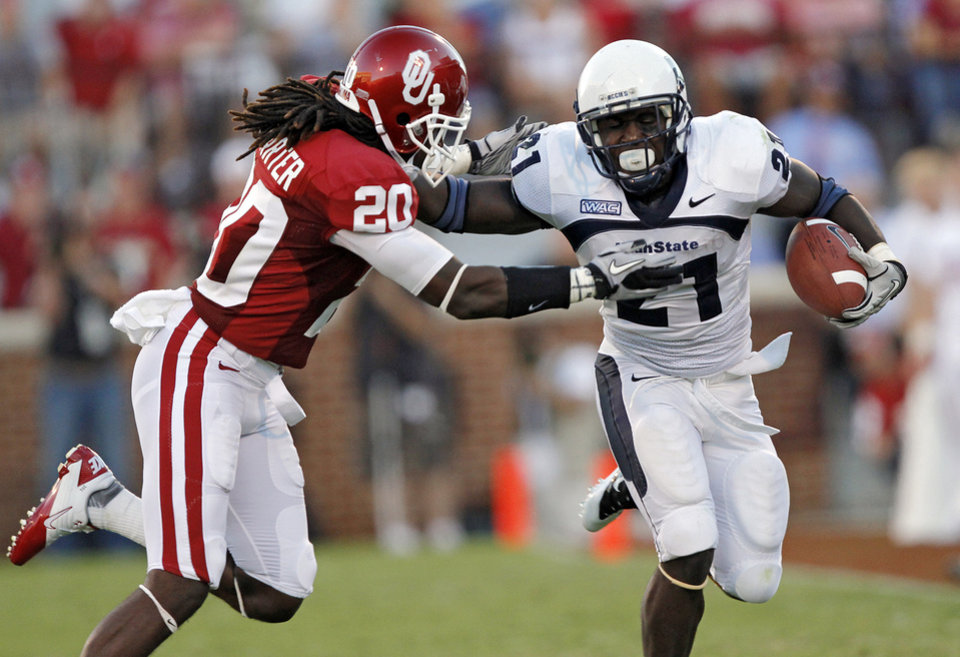 Photo - Utah State's Derrvin Speight (21) runs past Oklahoma's Quinton Carter (20) during the first half of the college football game between the University of Oklahoma Sooners (OU) and Utah State University Aggies (USU) at the Gaylord Family-Oklahoma Memorial Stadium on Saturday, Sept. 4, 2010, in Norman, Okla.   Photo by Chris Landsberger, The Oklahoman