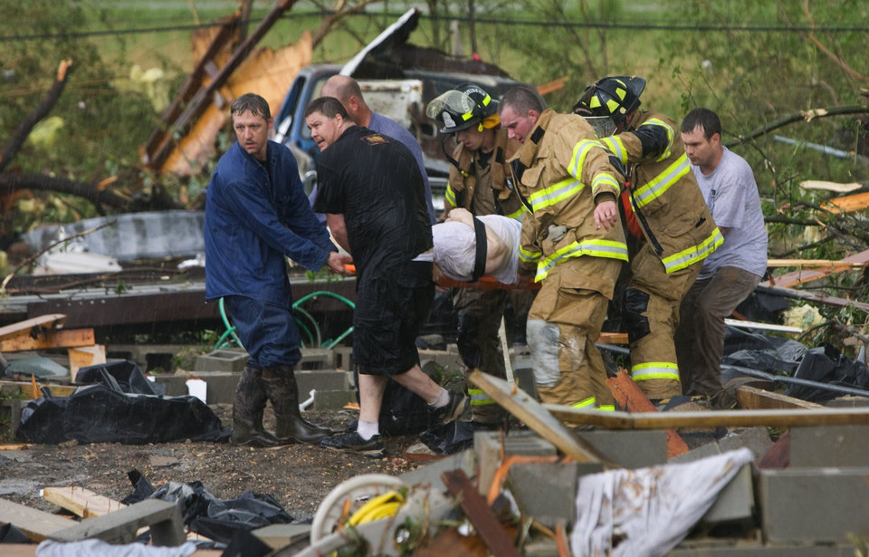 First responders carry an elderly woman away where they rescued her from the rubble of her home, after a tornado struck, Wednesday, April 27, 2011 in Phil Campbell, Ala. (AP Photo/TimesDaily, Daniel Giles)