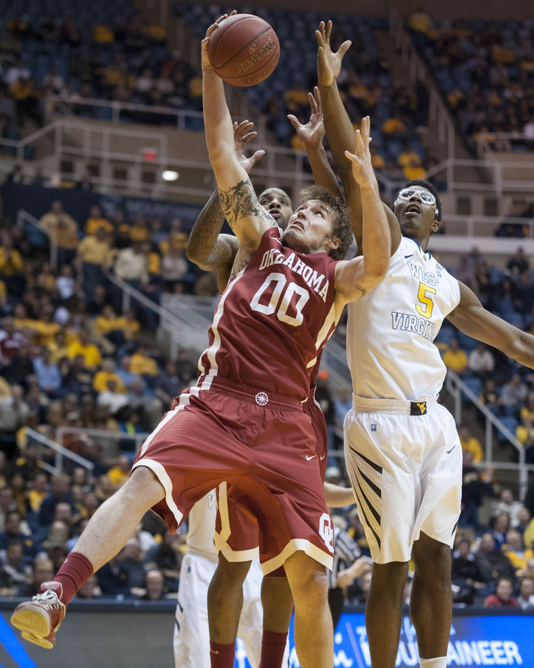 Oklahoma's Ryan Spangler,  front left, battles West Virginia's Devin Williams for a rebound during the second half of an NCAA college basketball game on Wednesday, Feb. 5, 2014, in Morgantown, W.Va. West Virginia won 91-86 in overtime. (AP Photo/Andrew Ferguson)