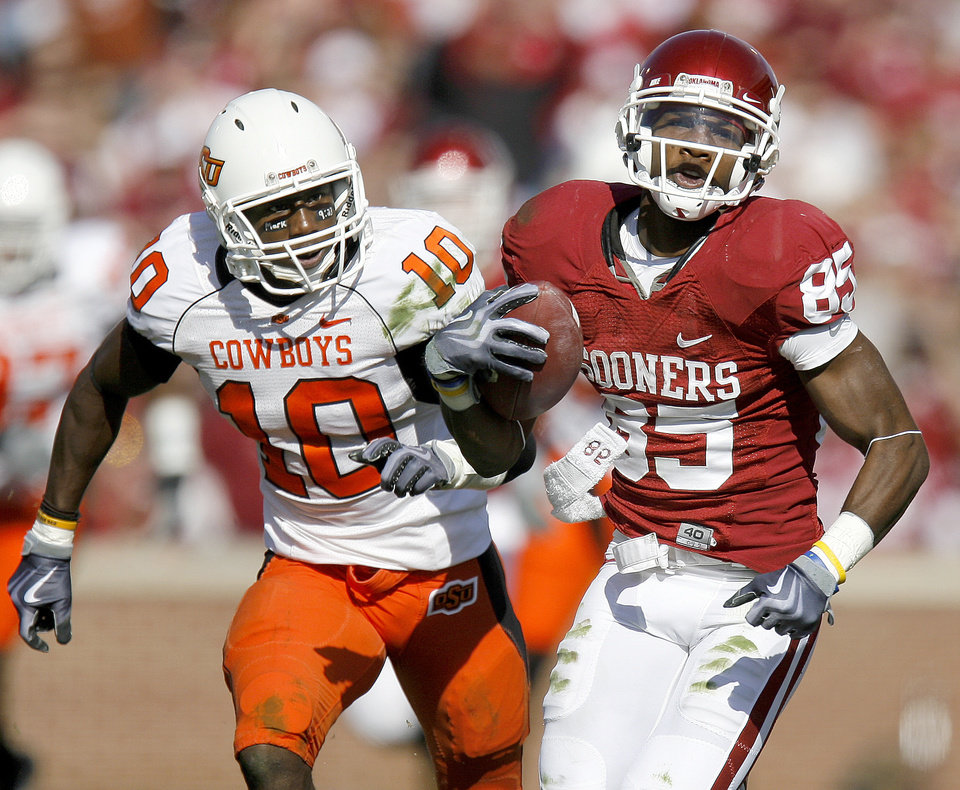 Photo - OU's Ryan Broyles runs from OSU's Markelle Martin after a catch during the first half of the Bedlam college football game between the University of Oklahoma Sooners (OU) and the Oklahoma State University Cowboys (OSU) at the Gaylord Family-Oklahoma Memorial Stadium on Saturday, Nov. 28, 2009, in Norman, Okla.
