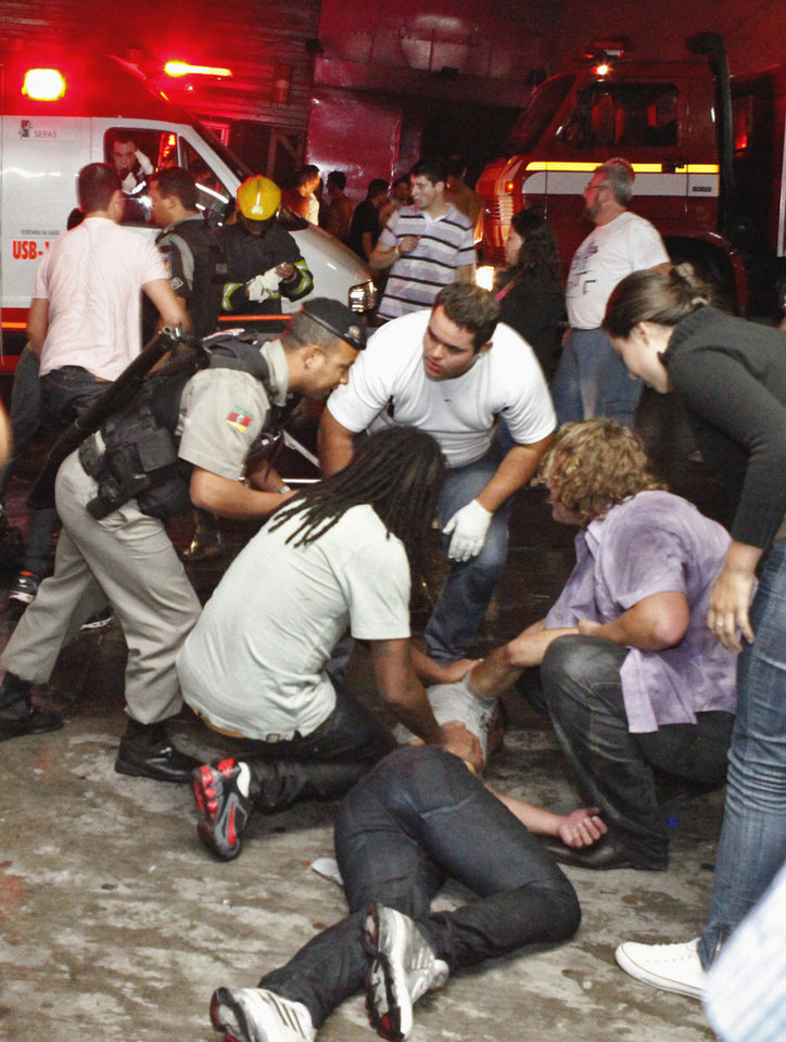 Photo - ALTERNATIVE CROP OF XSI103.- People help an injured man, victim of a fire in a club in Santa Maria city, Rio Grande do Sul state,  Brazil,  Sunday, Jan. 27,  2013.  According to police more than 200 died in the devastating nightclub fire in southern Brazil.  Officials say the fire broke out at the Kiss club in the city of Santa Maria while a band was performing. At least 200 people were also injured. (AP Photo/Agencia RBS)