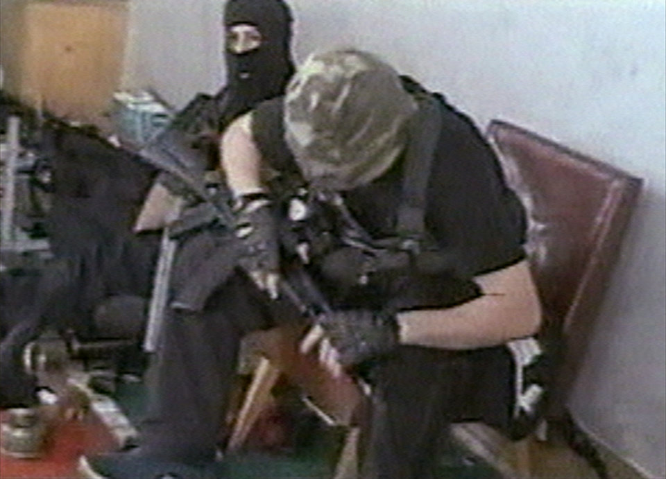 Photo - FILE - Hostages sit with their weapons in the school in Beslan, Russia taken  in this undated image from television during the early part of the siege which began on  Sept. 1, 2004 and ended with over 300 people dead. Two suspects in the Boston Marathon bombing have been identified to The Associated Press as coming from a Russian region near Chechnya  In the past, insurgents from Chechnya and neighboring restive provinces in the Caucasus have been involved in terror attacks in Moscow and other places in Russia. (AP Photo/NTV-Russian Television Channel, File)