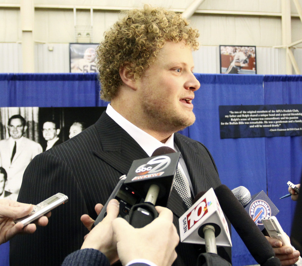 Photo - Buffalo Bills center Eric Wood answers questions from the media during a public memorial and remembrance being held inside the NFL football team's fieldhouse for Buffalo Bills owner Ralph C. Wilson in Orchard Park, N.Y., Saturday, April 5, 2014. Wilson, the team's founder and sole owner, died March 25. (AP Photo/Nick LoVerde)