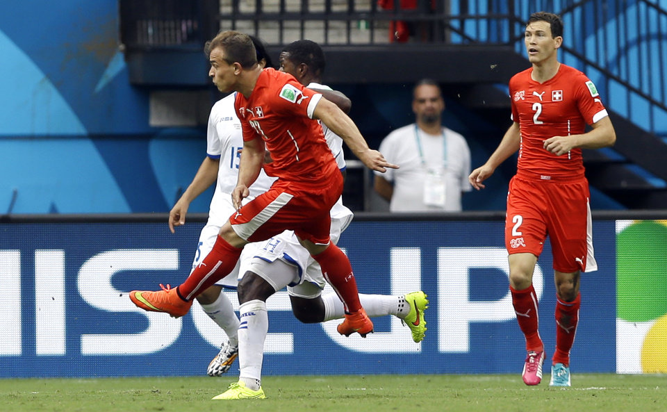 Photo - FILe - In this June 25, 2014 file photo, Switzerland's Xherdan Shaqiri, left, scores the opening goal during the group E World Cup soccer match between Honduras and Switzerland at the Arena da Amazonia in Manaus, Brazil. Shaqiri collected the ball outside the top right corner of the area, dribbled to avoid a pair of defenders and then launched a curling shot toward the top left corner of the net that went in off the underside of the crossbar. (AP Photo/Kirsty Wigglesworth, File)