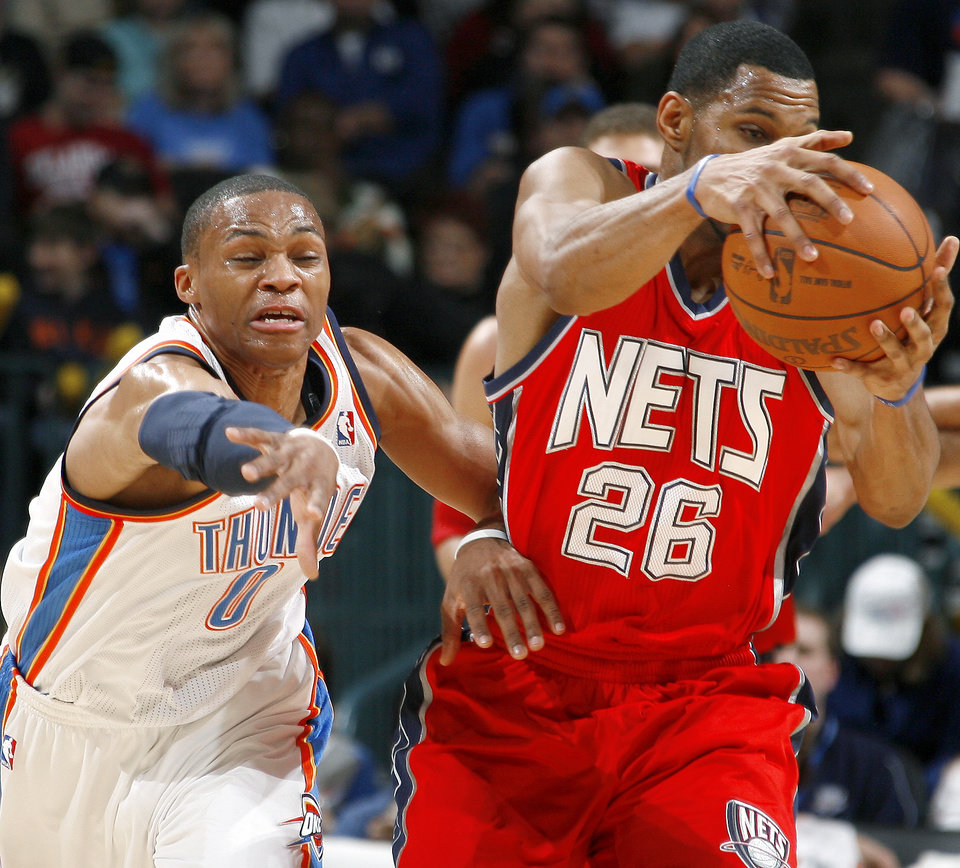 Photo - Oklahoma CIty's Russell Westbrook goes for the ball beside New Jersey's Stephen Graham during the NBA basketball game between the Oklahoma City Thunder and the New Jersey Nets at the Oklahoma City Arena, Wednesday, Dec. 29, 2010.  Photo by Bryan Terry, The Oklahoman