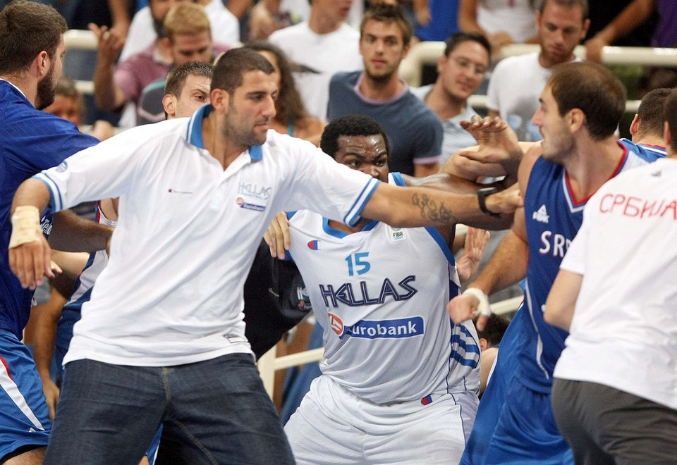Photo - Greek center Sofoklis Schortsanitis, center, tries to kick Serb center Nenad Krstic, of the NBA's Oklahoma City Thunder, right, as Greek center Yannis Bouroussis, who did not take part in the game, tries to stop them during a basketball game for the Acropolis tournament at the indoor Olympic stadium of Athens, Thursday, Aug. 19, 2010.The friendly Acropolis basketball tournament never finished as the last game, between Serbia and Greece, was abandoned with 2:40 to go when a fight broke out and the benches cleared. (AP Photo/Newsports, Nikos Chalkiopoulos)